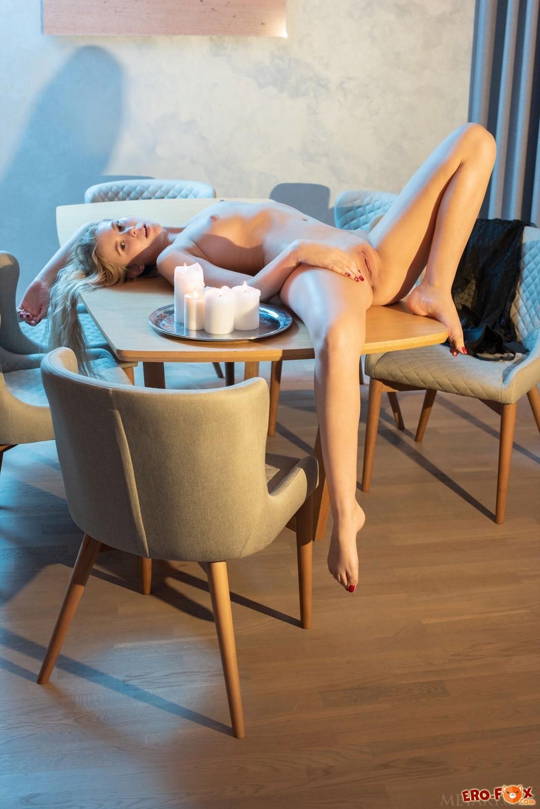 Милашка с бритой писькой голая лежит на столе - фото