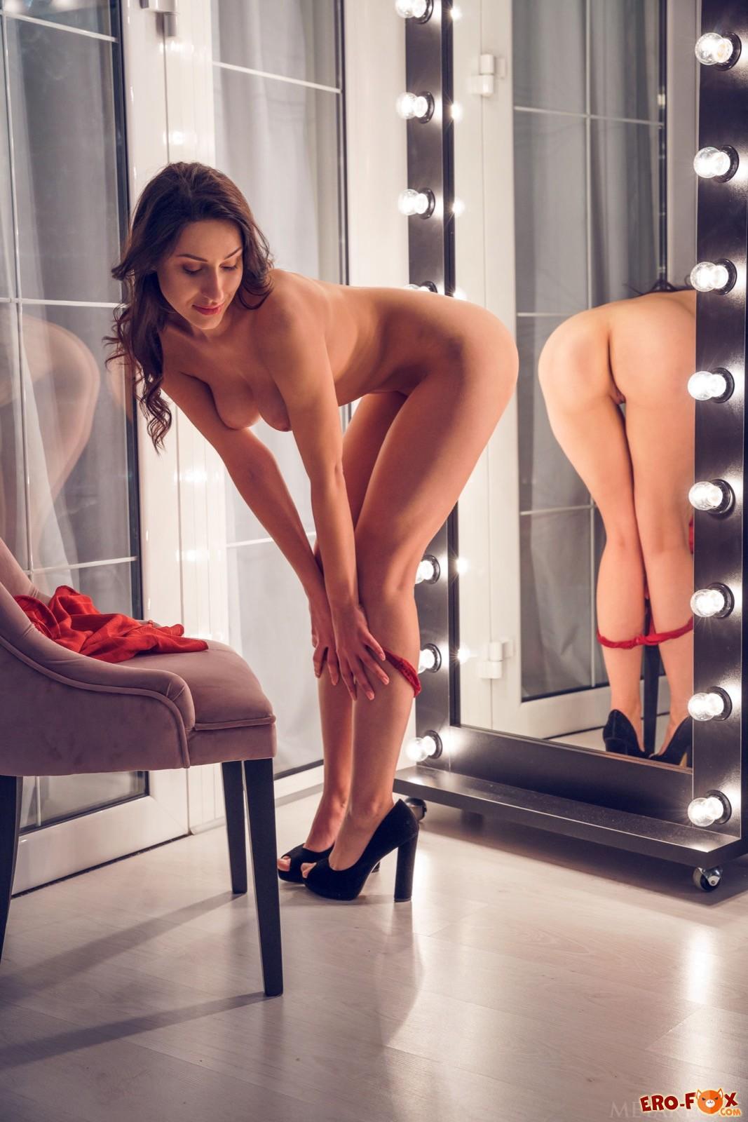Разделась перед зеркалом и смотрит на голую попу - фото
