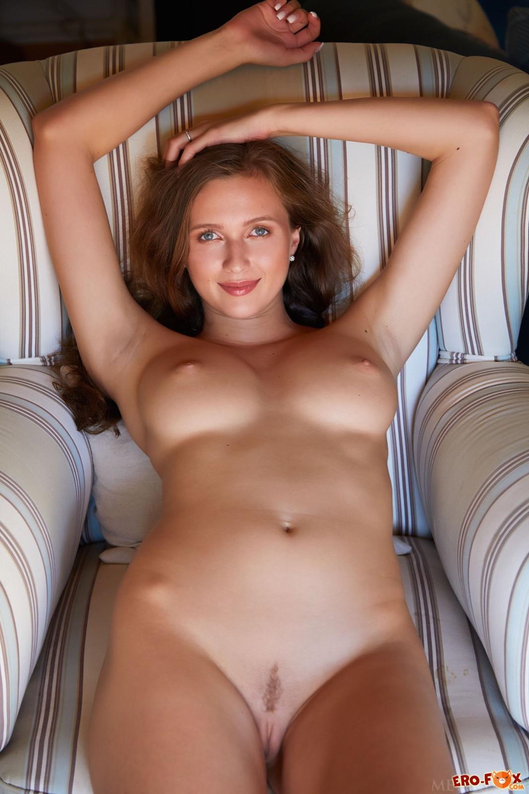 Голая девушка с длинными ногами в кресле - фото