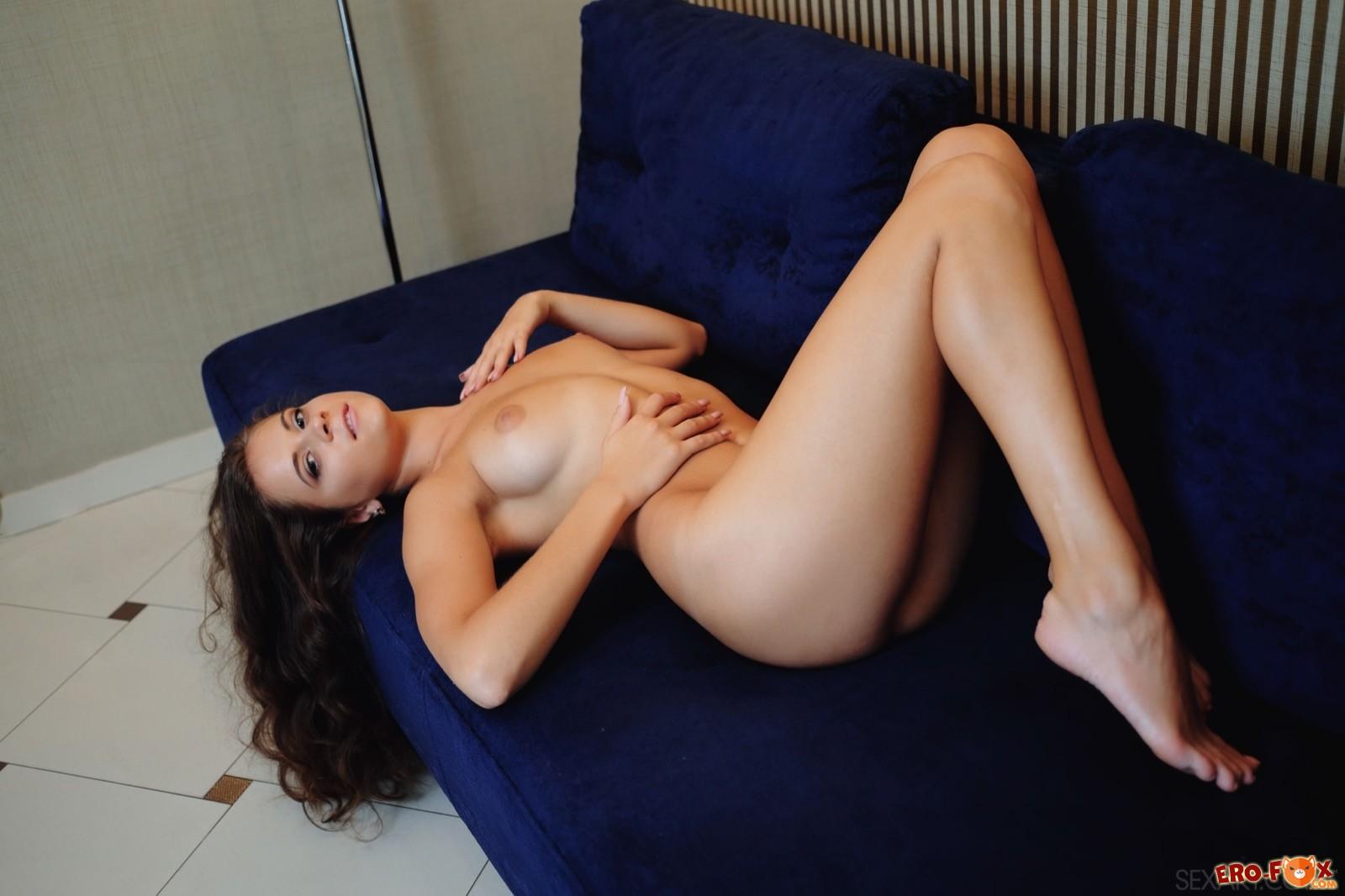 Нагая милашка поглаживает письку и попку на диване - фото
