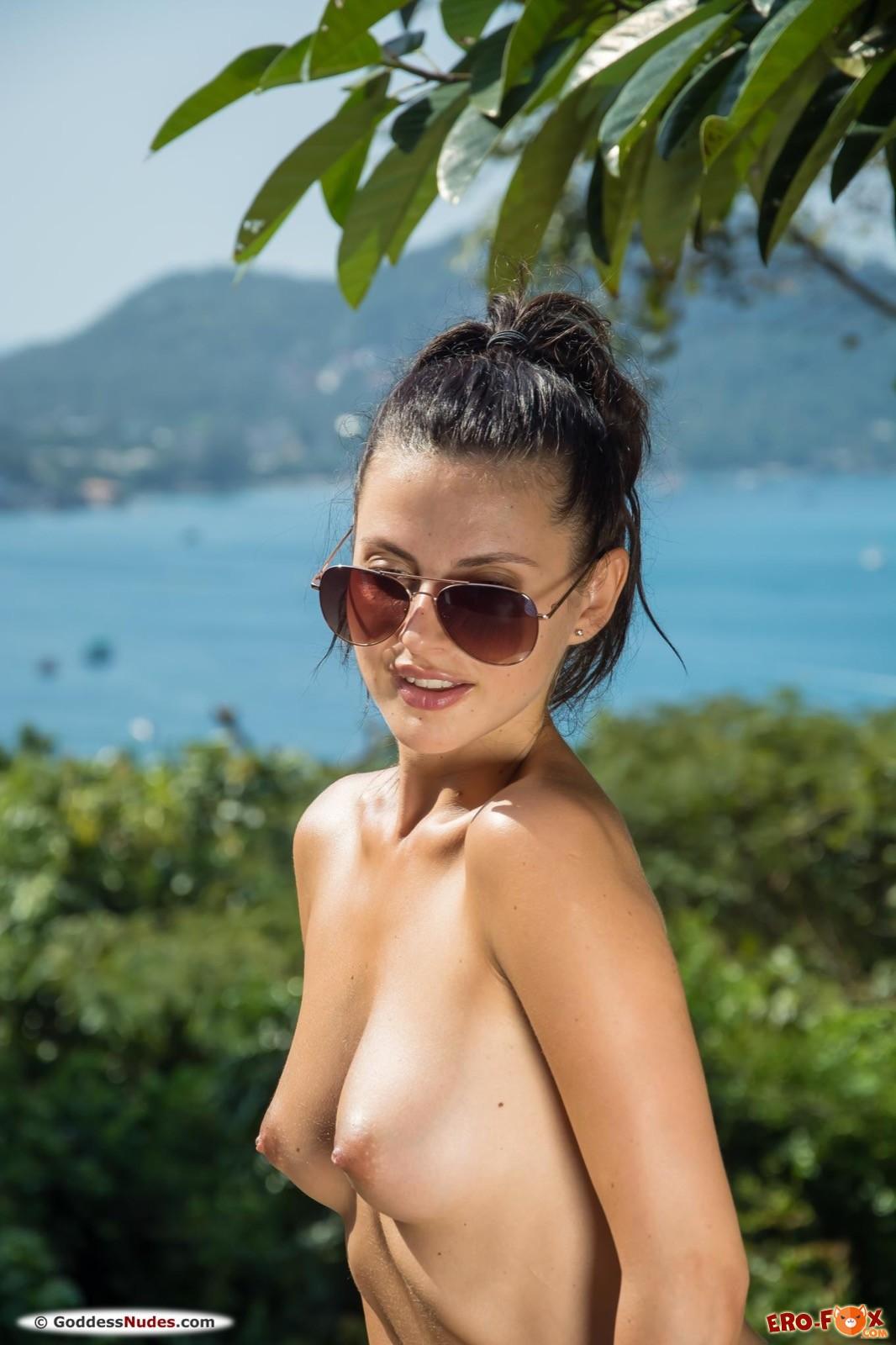 Голая девушка в солнцезащитных очках - фото