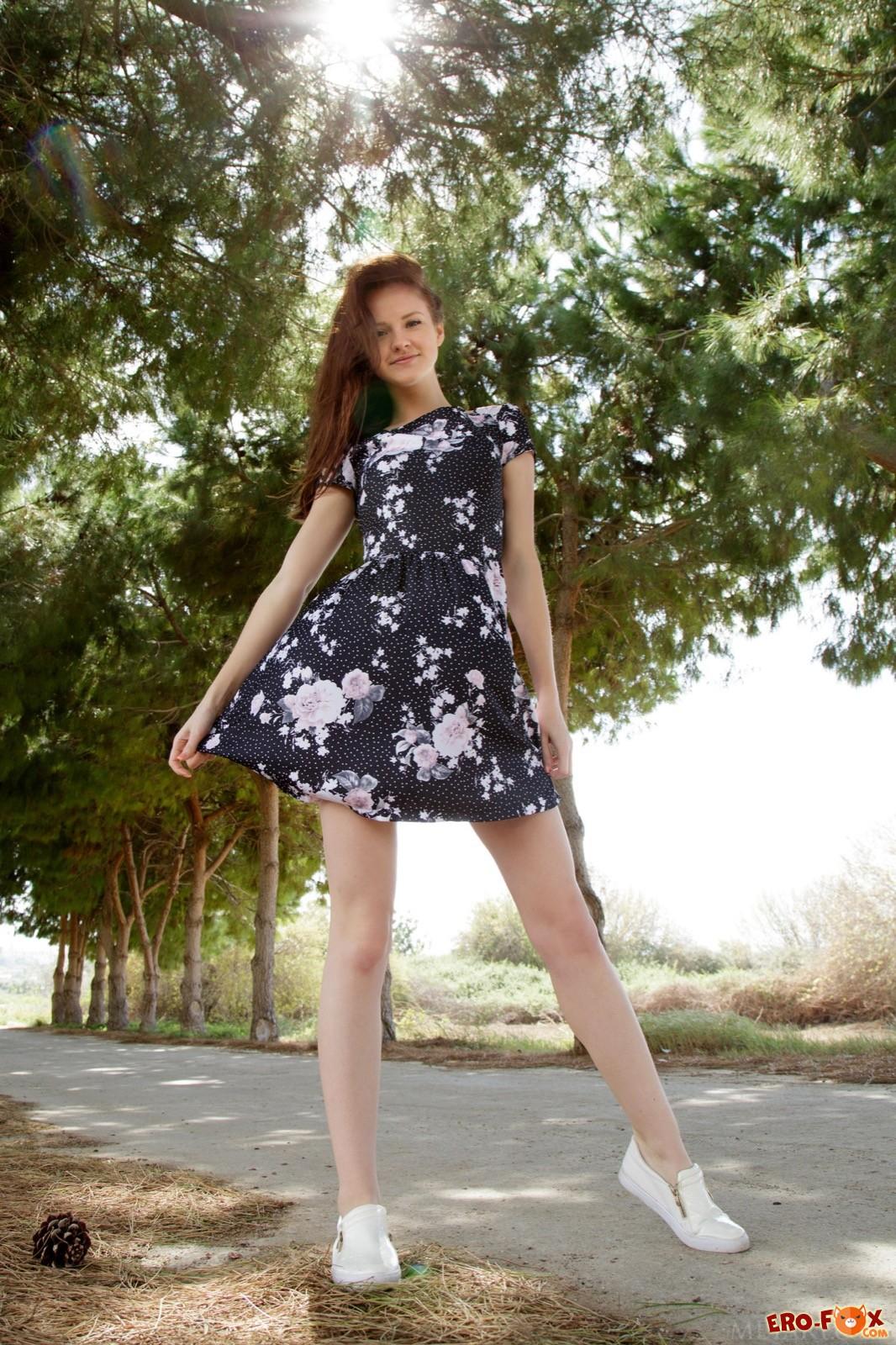 Молодая шатенка снимает платье гуляя по дороге - фото