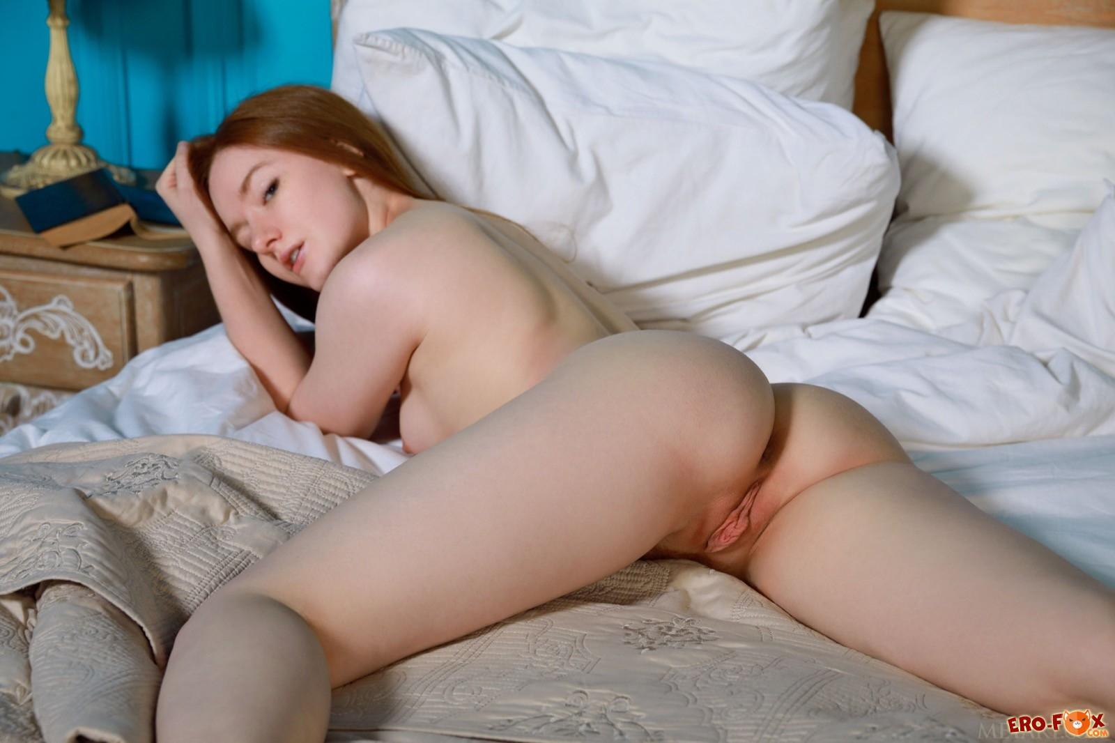 Голая рыжая девка с большой красивой попой в постели - фото
