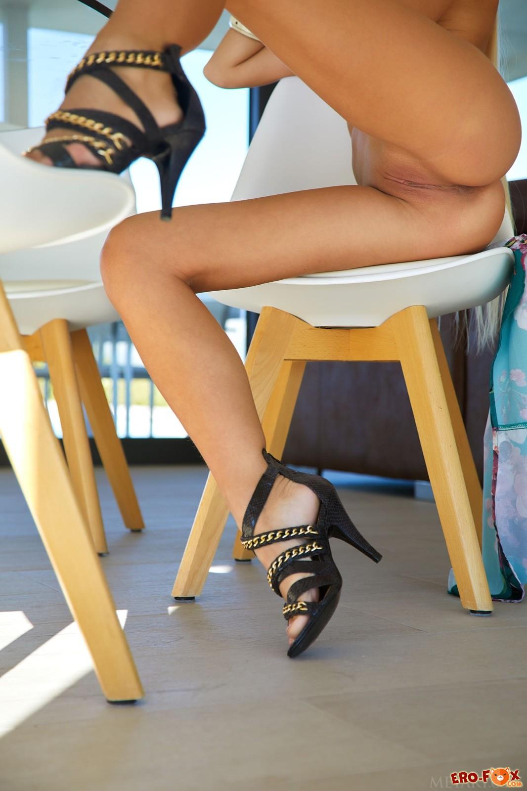 Блондинка без трусов раздвигает длинные ноги на стуле - фото
