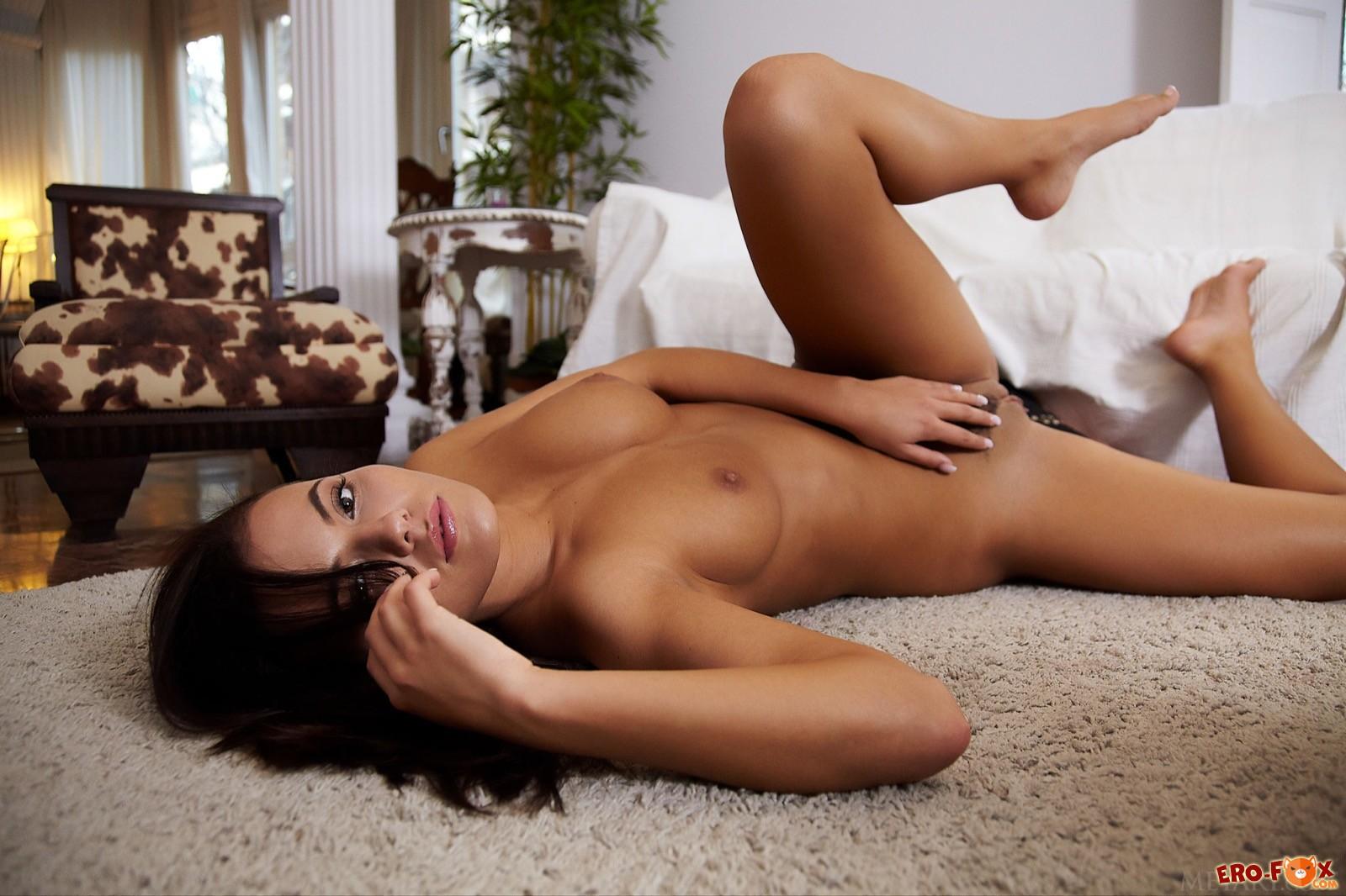 Загорелая голая девица показывает себя лежа на полу - фото