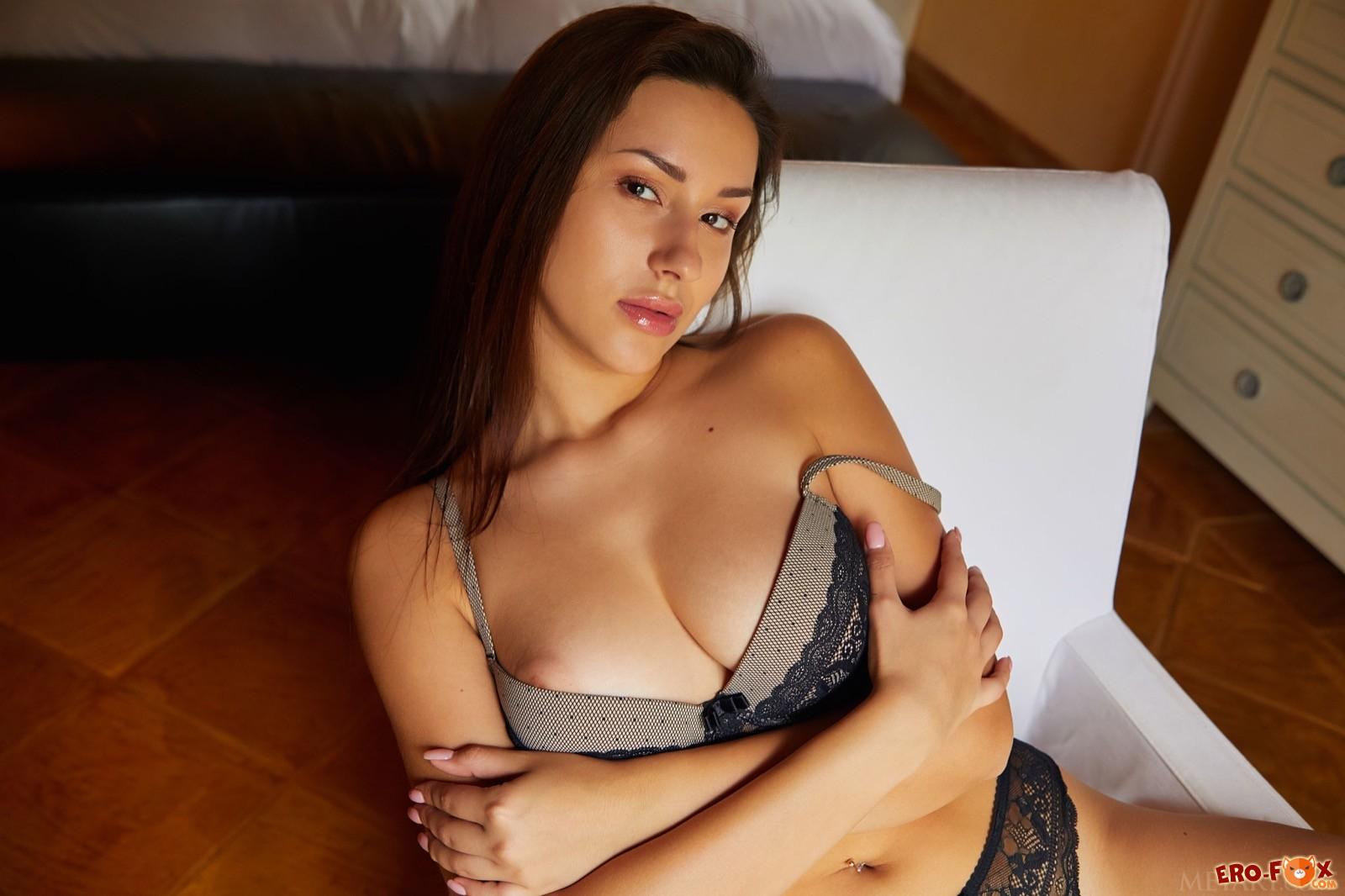 Эффектная девушка с упругой грудью позирует на стуле - фото