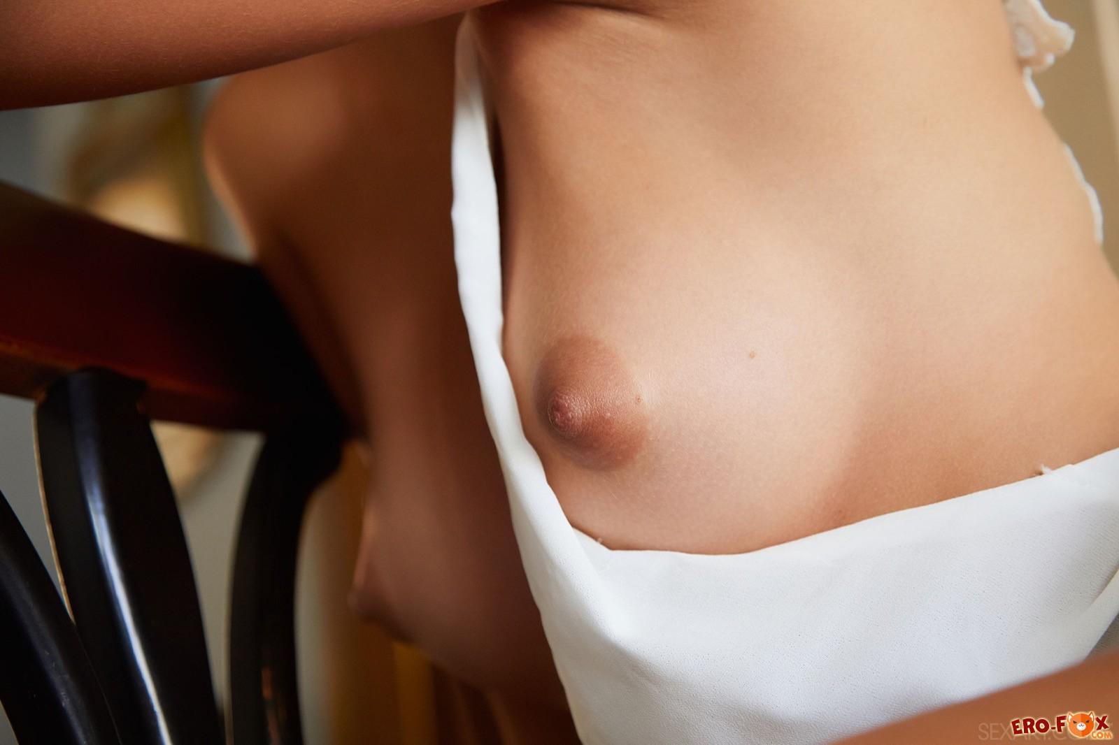 Нежная милашка в платье оголилась сидя на стуле - фото