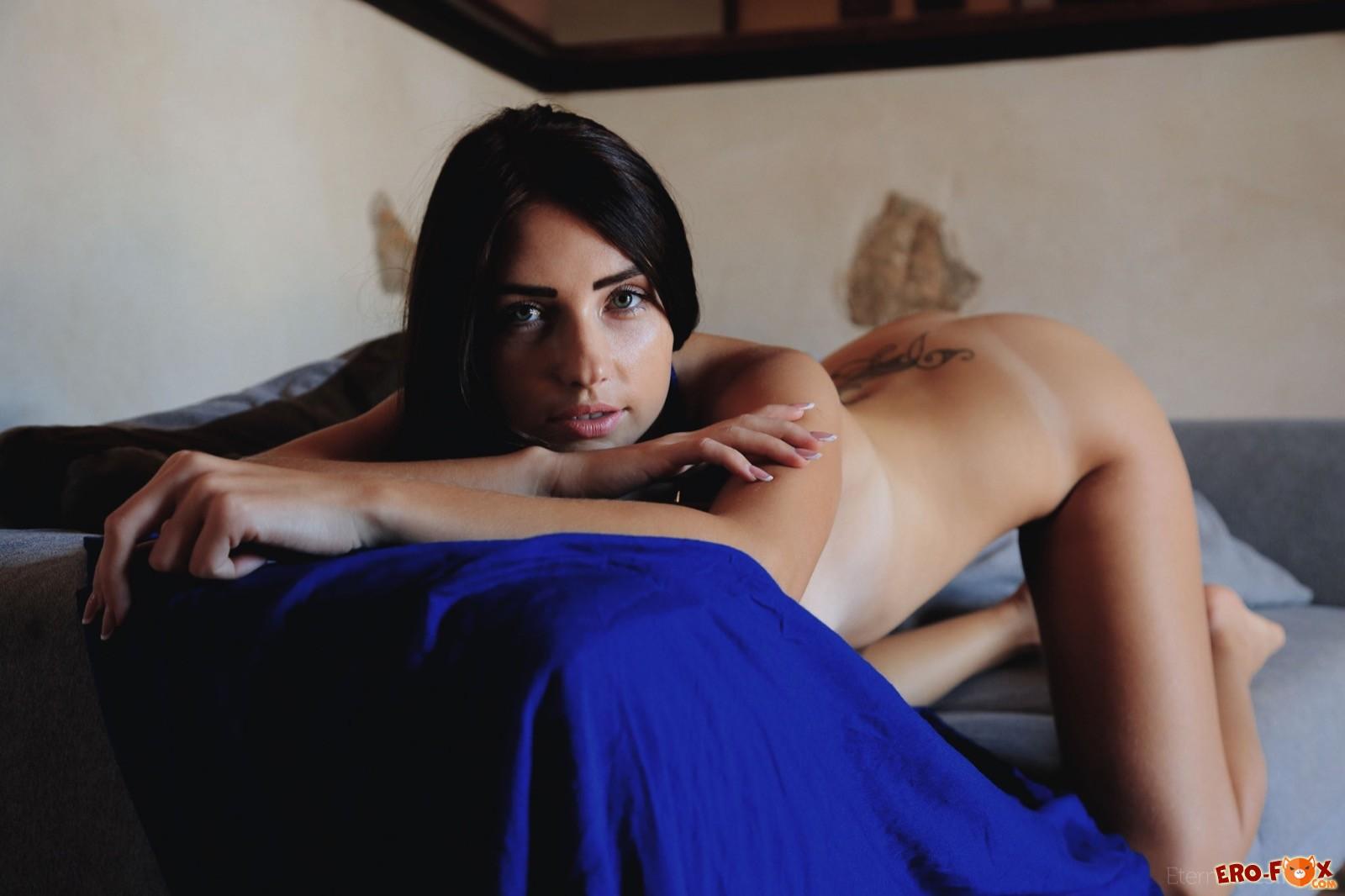 Раздетая сексапильная девица позирует на диване - фото