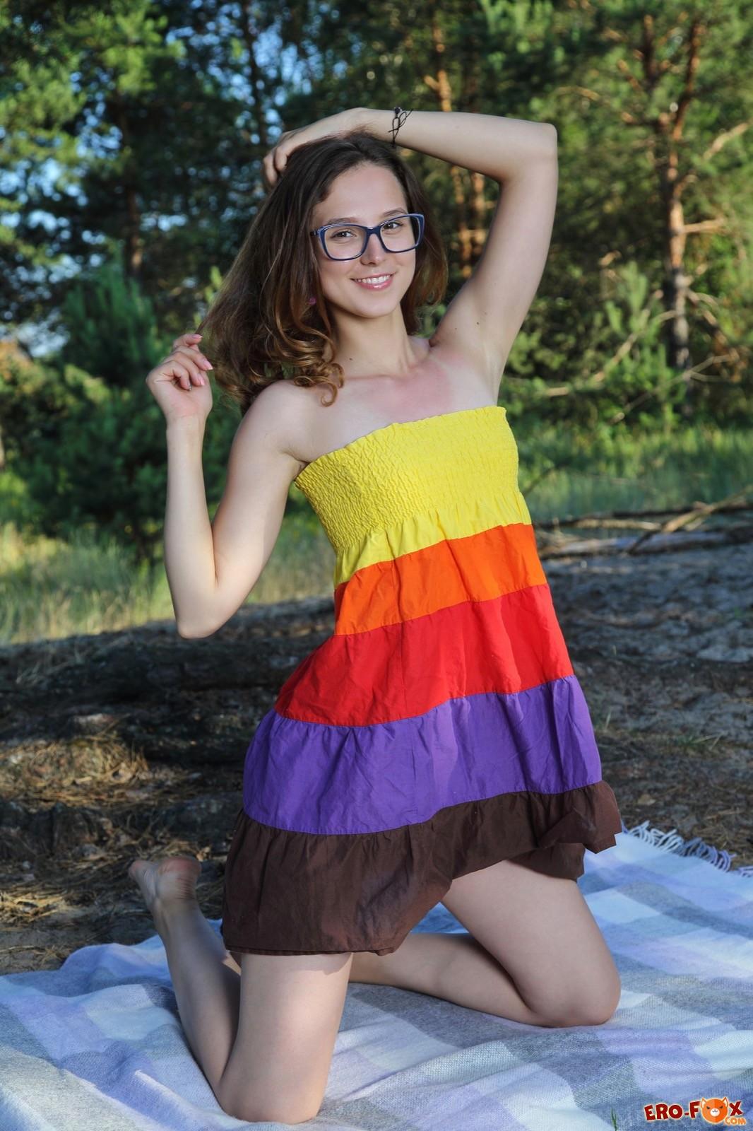 Молодая милашка в очках снимает платье в лесу - фото