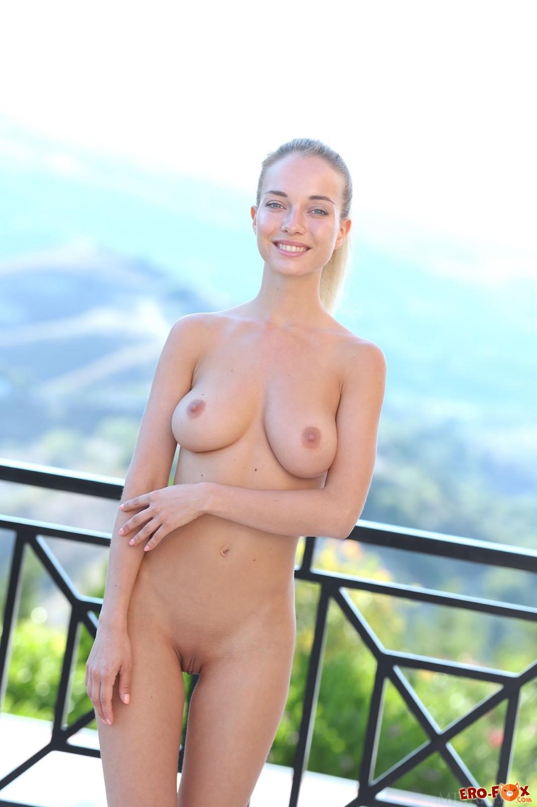 Симпатичная девушка стягивает нижнее бельё на балконе - фото