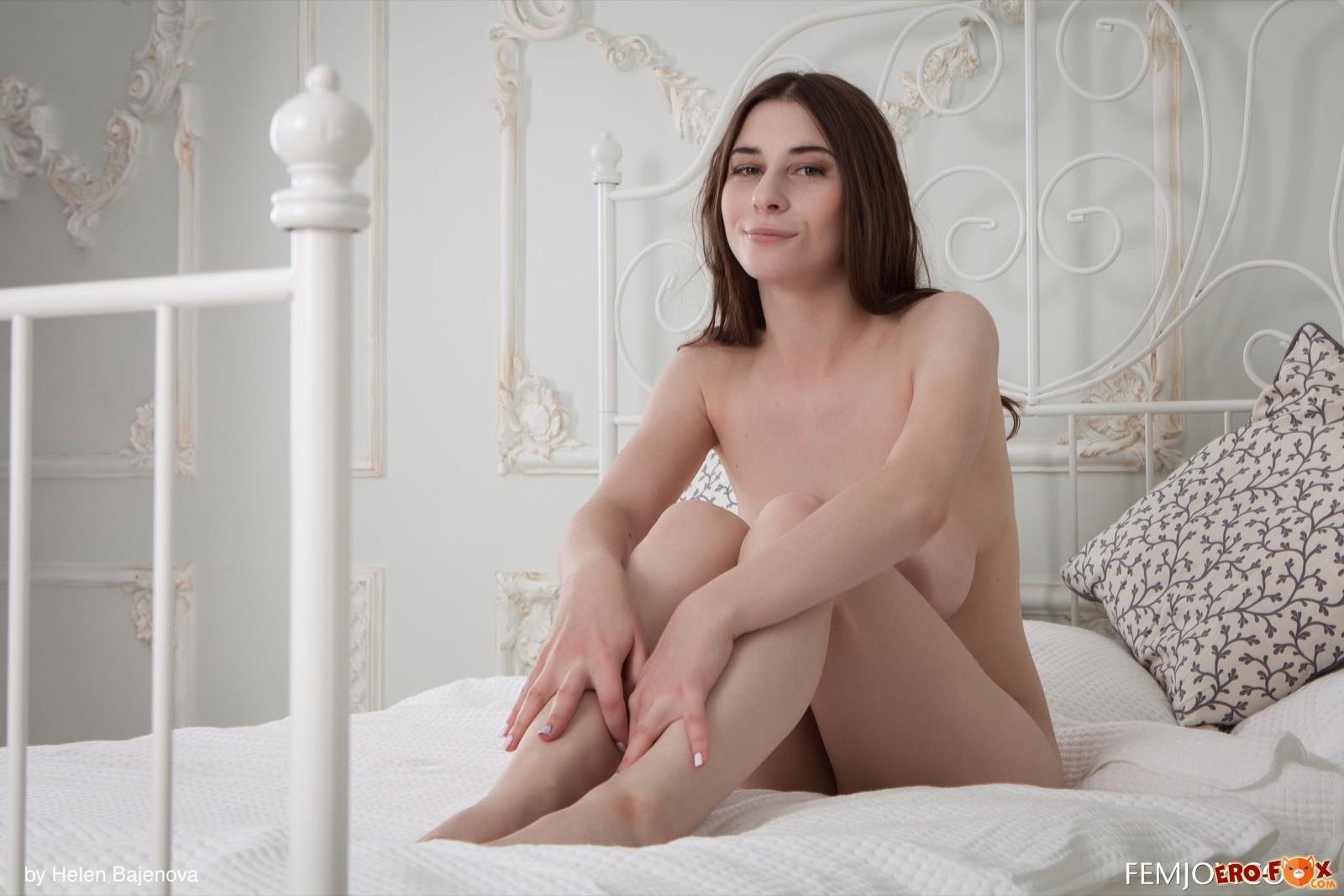 Нагая милашка с крупными висячими сиськами в постели - фото